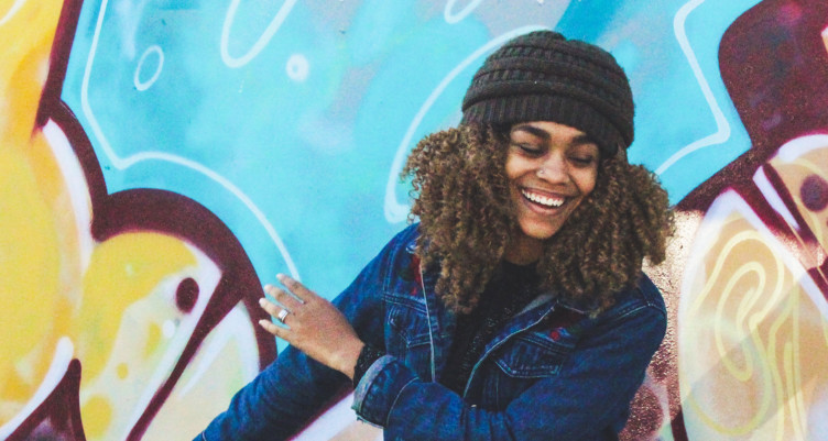 Woman wearing beanie smiling in front of colorful wall